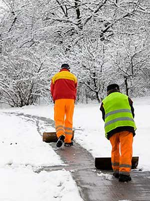 Workers plowing snow off the sidewalk