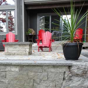 Interlocking patio with red Muskoka chairs. Armour wall in front and natural stone fire pit can be seen on the left