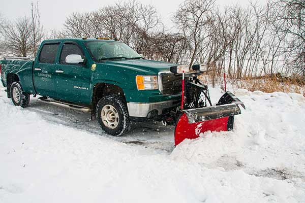 Green Acorn Landscaping truck snow plowing a parking lot.