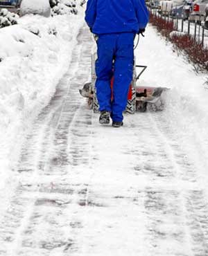 Worker clears snow from sidewalk
