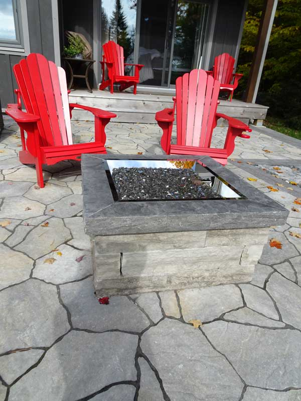 Natural Stone Fire Pit with a cap installed on interlocking patio.