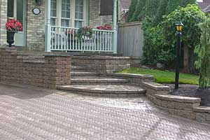 Landscaping Design that uses a natural stone wall edging between garden and the driveway
